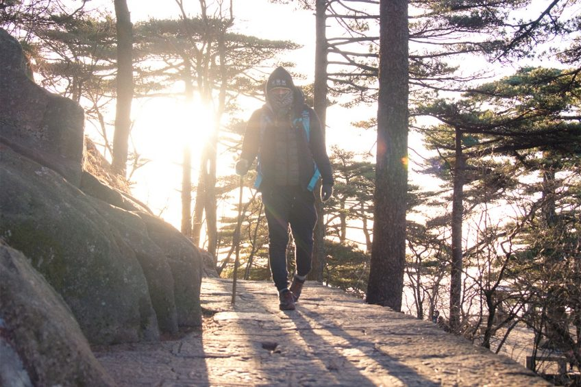 man hiking in huangshan with the sunrising behind